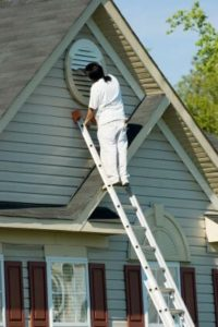 Painter painting a Window — House Painting in Lincoln, CA